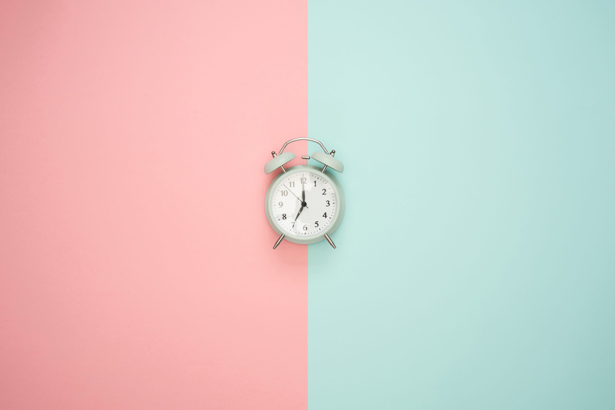 A blue alarm clock on a pink and blue background.